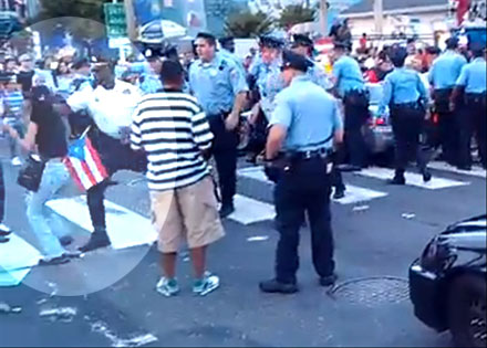 (Lt. Jonathan Josey strikes Aida Guzman in the face during an incident after the 2012 Puerto Rican Day parade.  File photo)