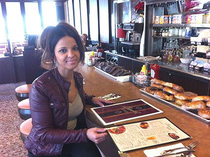 """(Roula Kosmatos, a waitress at the Llanerch Diner, notes that prices on the genuine menu, left, are lower than prices on the """"prop"""" menu used in the movie, right.  Credit: John McDevitt)"""