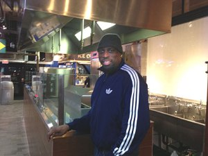 (KeVen Parker at his soul food stand in the Reading Terminal Market.  Credit: Hadas Kuznits)