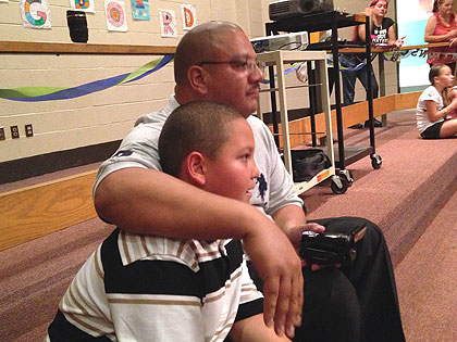 (Erasmo Santiago with his father at the Springboard Collaborative awards ceremony at McKinley Elementary School.  Credit: Cherri Gregg)