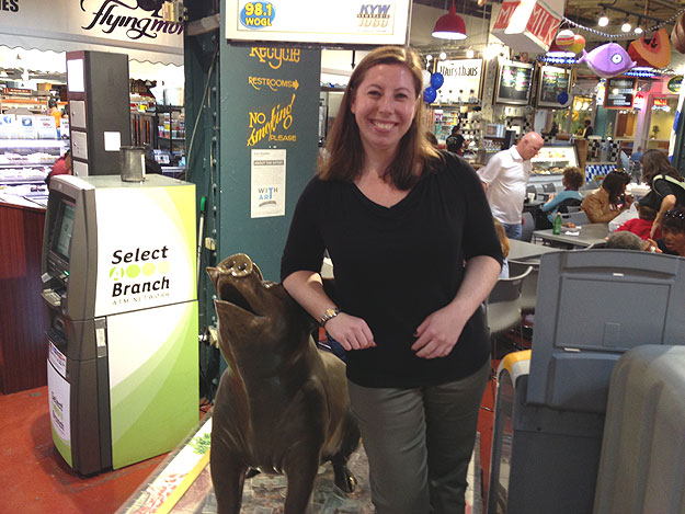 (Sarah Levitsky leans on the bronze sculpture of Philbert the Pig, the Reading Terminal Market mascot. Photo by Hadas Kuznits)