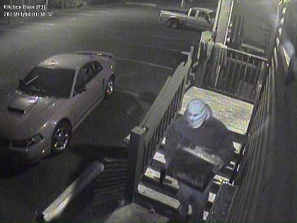 (A  masked robber carries a safe down the stairs behind the Whitpain Tavern.  Surveillance photo provided)