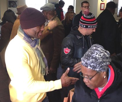 (Champion boxer Bernard Hopkins, left, greets a visitor during the turkey giveaway.  Credit: Steve Tawa)