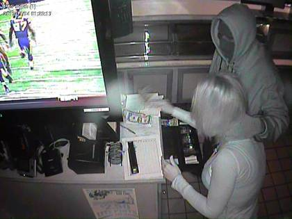 (Robber holds an employee by the neck while rifling the cash register at the Whitpain Tavern.  Surveillance photo provided)