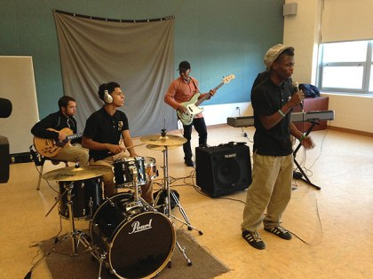 (Singer Jeffrey Williams, front, is accompanied by fellow students and visiting teacher Kevin Eubanks, in orange shirt.  Credit: Cherri Gregg)
