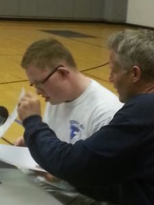 Kevin Grow signs on the dotted line next to Sixers Head Coach Brett Brown. (credit: Dan Wing/KYW)