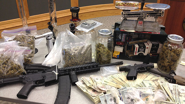 (Evidence seized during the investigation included cash, drugs, and weapons.  Photo by Brad Segall)