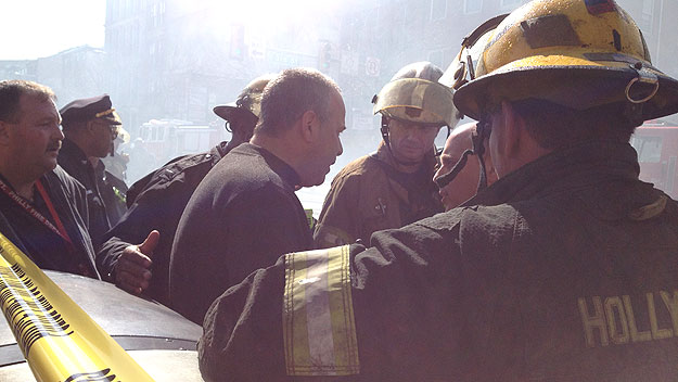 (Suit Corner owner Gary Ginsberg, center, talks with firefighters.  Photo by Pat Loeb)