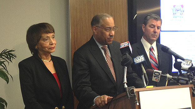 (Contractor Walter Logan, center, with his wife and his attorney, Mark Tanner.  Photo by Brad Segall)