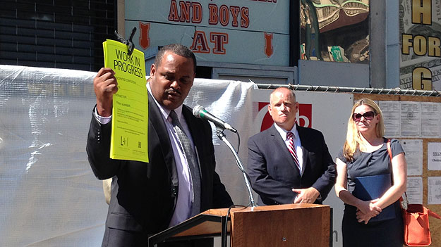 (L&I commissioner Carlton Williams shows an example of the type of new sign required for smaller construction sites in Philadelphia.  Photo by Mike Dunn)