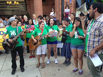 (Immigration reform advocates sing near anti-immigration protesters.  Photo by Cherri Gregg)