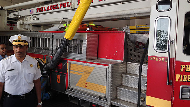 (Philadelphia fire commissioner Derrick Sawyer demonstrates how an exhaust hose can be connected to a running fire vehicle to vent fumes to the outside.  Photo by John McDevitt)