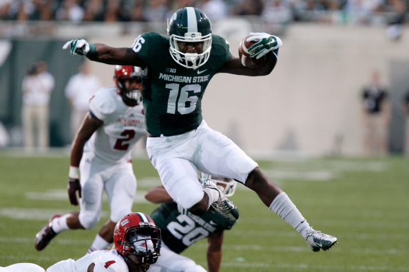 EAST LANSING, MI - AUGUST 29: Wide receiver Aaron Burbridge #16 of the Michigan State Spartans hurdles safety Folo Johnson #4 of the Jacksonville State Gamecocks on a 15-yard run during the first quarter at Spartan Stadium on August 29, 2014 in East Lansing, Michigan. (Photo by Duane Burleson/Getty Images)