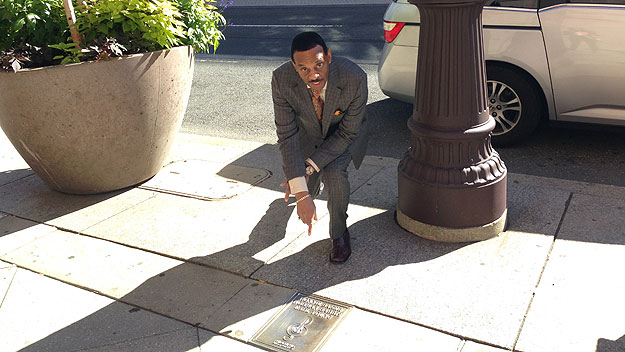 (Earl Young points to one of four bronze plaques placed in his honor along the Philadelphia Walk of Fame, on Broad Street.  Photo by John McDevitt)
