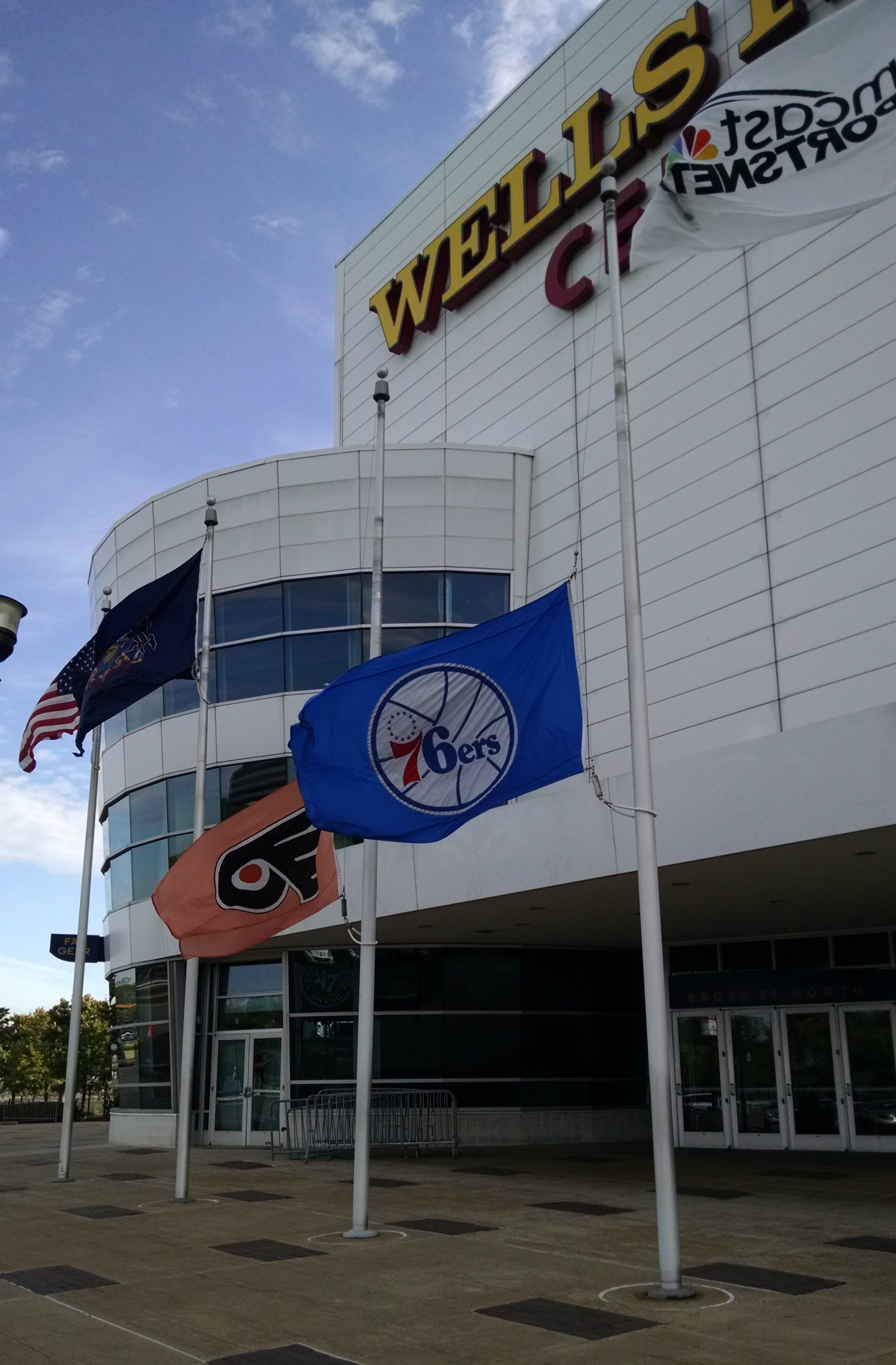 Flags fly at half-staff outside the Wells Fargo Center in Philadelphia in honor of Bill Campbell. Campbell, a sports broadcasting legend in Philadelphia, passed away on October 6, 2014. (credit: Ike Richman)