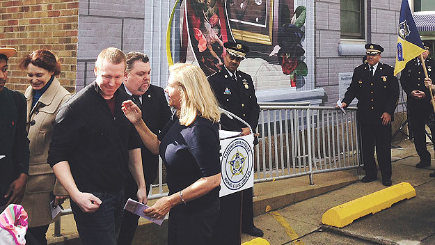 (Maureen Faulkner, widow of Officer Daniel Faulker, chats with artist Jonathan Laidacker at the dedication of Laidacker's mural honoring her husband.  Photo by Steve Tawa)