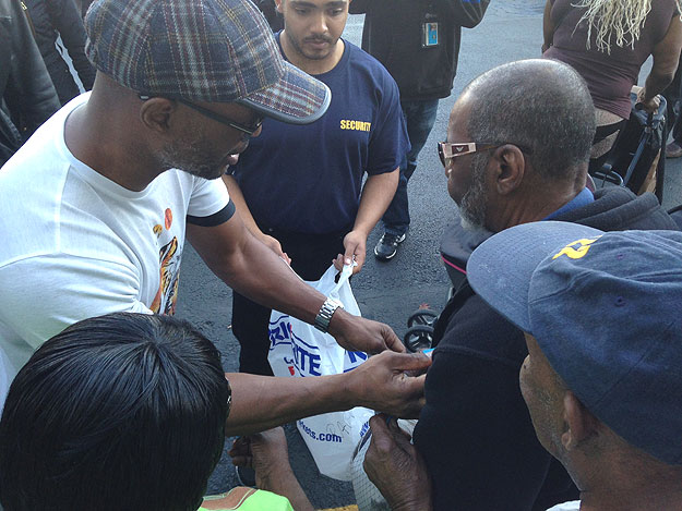 (Bernard Hopkins, in plaid hat at left, hands a bagged turkey to an area resident who waited in line.  Photo by Cherri Gregg)