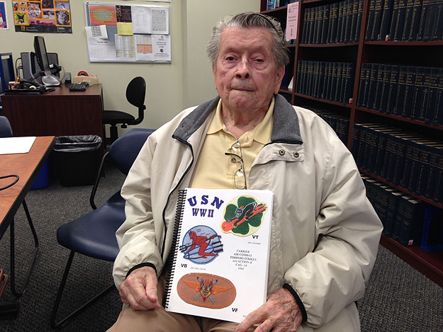 (Ward Driscoll holds a copy of his self-published collection of memoirs from World War II veterans including himself.  Photo by Cherri Gregg)