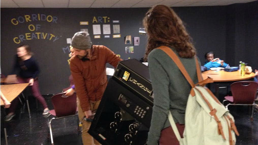 "Anna Sugrue shows Nic Esposito from The Head and The Hand Press where to put the book vending machine, in a student lounge called ""Corridor of Creativity."" (Credit: Pat Loeb)"