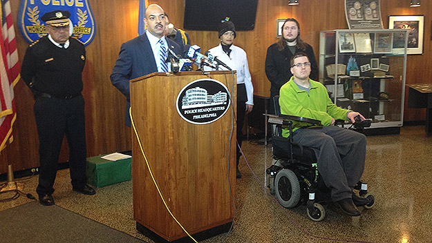 (Phila. DA Seth Williams warns against shooting guns to celebrate New Year's Eve.  Phila. police commissioner Charles Ransey is at far left.  Seated at right is Joe Jaskolka, who was paralyzed by a stray bullet on New Year's Eve 1998.  Photo by Steve Tawa)