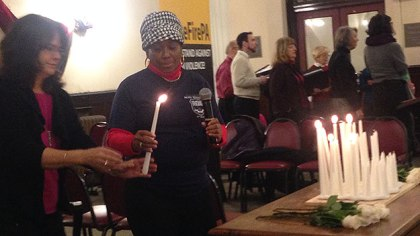 (Wayne Lipscomb, the mother of slain Philadelphia police officer Moses Walker, lights a candle in memory of her son.  Photo by John McDevitt)