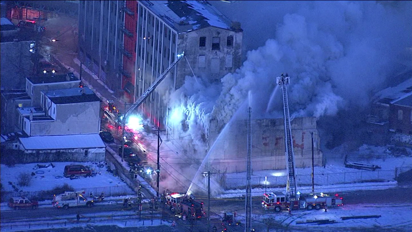 Fire in West Kensington early Tuesday burns through a building near the Market Frankford Line. (Credit: CBS3)