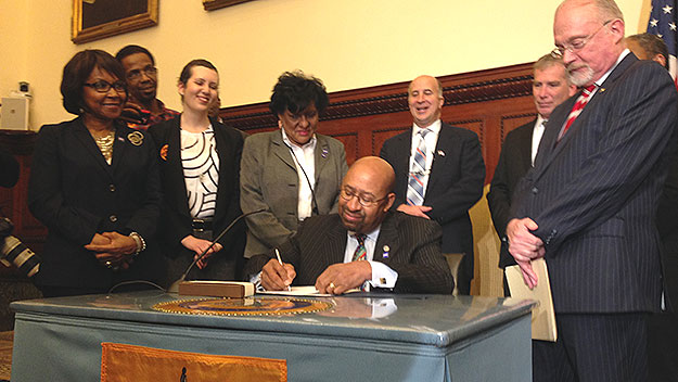 (Surrounded by supporters of the measure, Mayor Nutter signs the new paid sick leave legislation into law.  Photo by Mike Dunn)