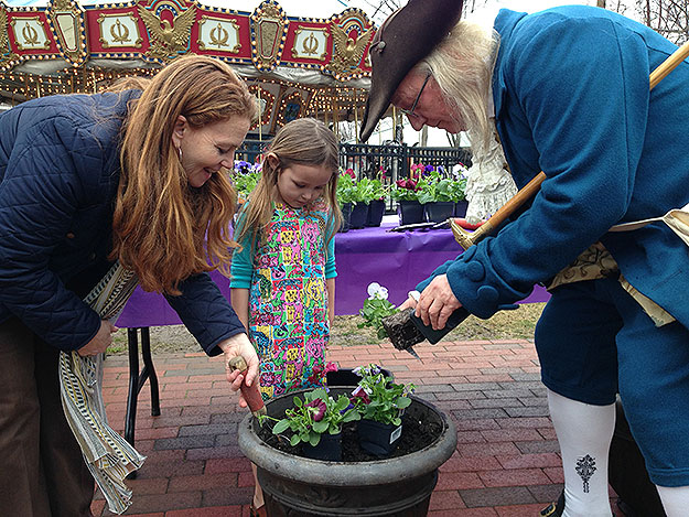"""(Amy Needle, president of Historic Philadelphia, left, and """"Ben Franklin"""" help a young visitor to Franklin Square plant flowers.  Photo by Paul Kurtz)"""