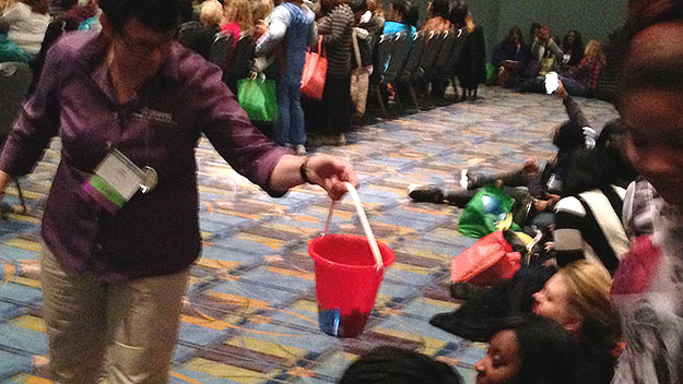 "(A child's bucket is passed to collect ""Pennies for Pre-K.""  Photo by Paul Kurtz)"