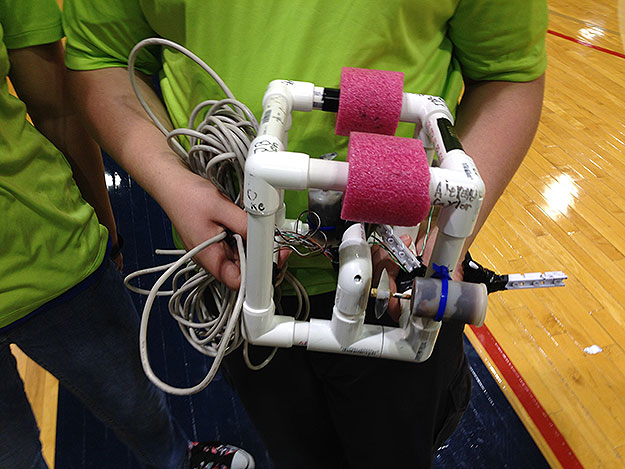 (A member of a team from Lancaster, Pa. shows their underwater robotics device.  Photo by John McDevitt)