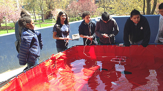 (Students from the Stewart Middle School, in Norristown, test their device in a practice pool.  Photo by John McDevitt)