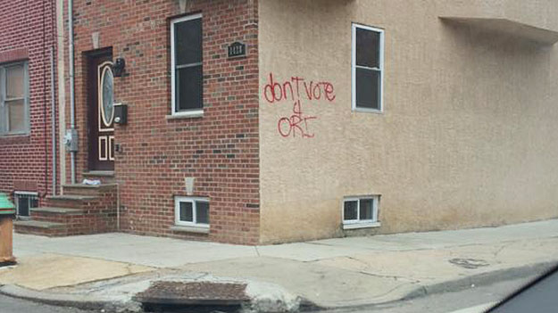 """(The wall of a neighborhood home is spray-painted """"Don't Vote 4 Ori.""""    Photo provided)"""