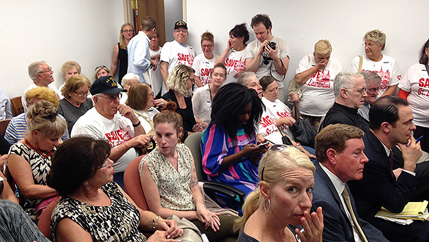 """(Many wearing matching """"Save St. Laurentius"""" shirts, community members wait to hear the vote of the Historical Commission committee.  Photo by Cherri Gregg)"""
