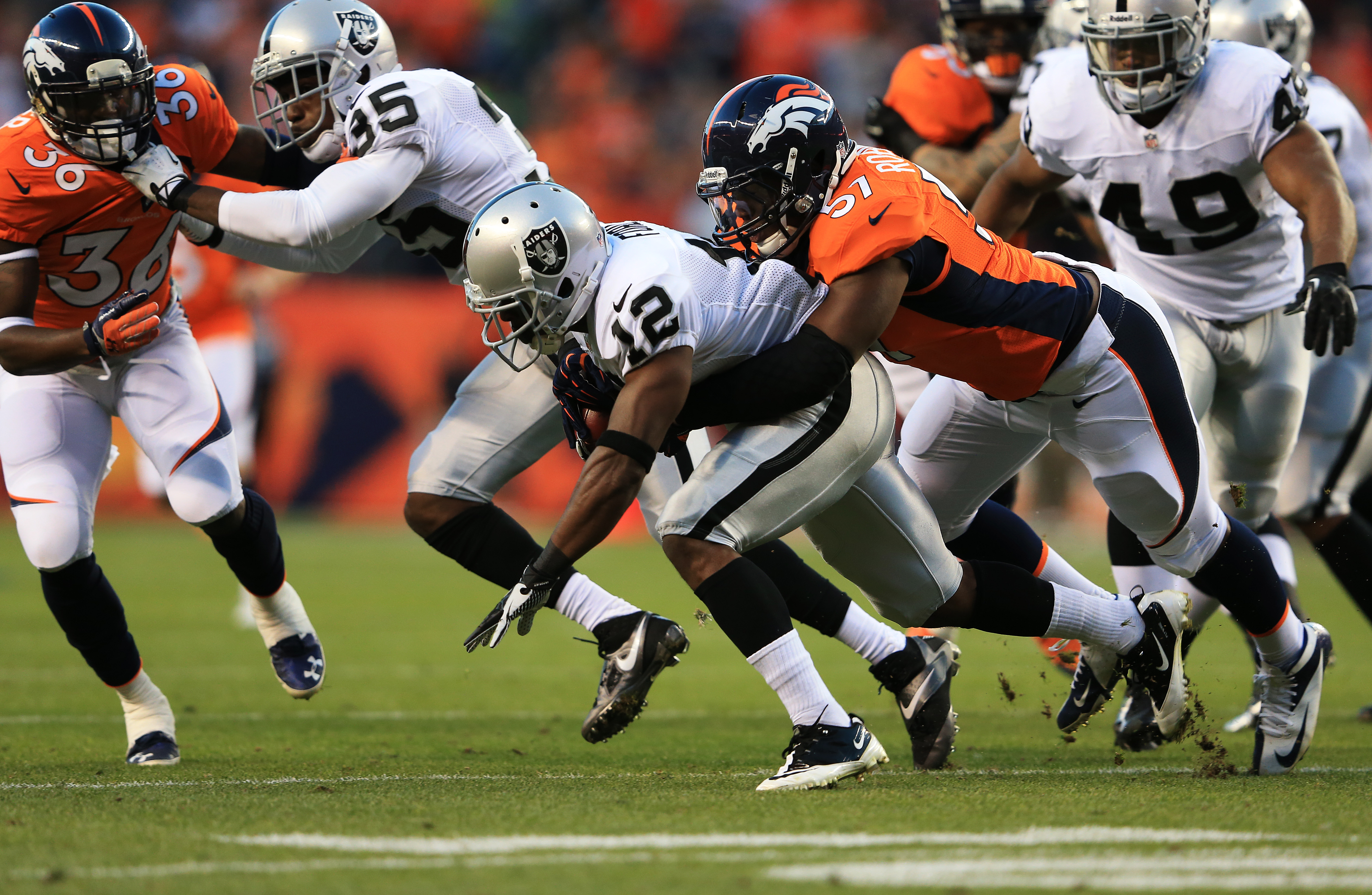 DENVER, CO - SEPTEMBER 23:   Jacoby Ford #12 of the Oakland Raiders is tackled by Adrian Robinson #57 of the Denver Broncos as he returns the opening kickoff at Sports Authority Field at Mile High on September 23, 2013 in Denver, Colorado.  (Photo by Doug Pensinger/Getty Images)