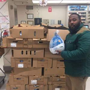 Picture of Hadrick holding turkey at their annual Turkey Drive (Credit: NMOE)