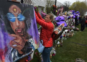 A Prince fan attaches flowers to a memorial wall as she pays her respects outside the Paisley Park residential compound in Minneapolis, Minnesota, on April 22, 2016. Prince died April 21, 2016. / AFP / Mark Ralston (Photo credit should read MARK RALSTON/AFP/Getty Images)