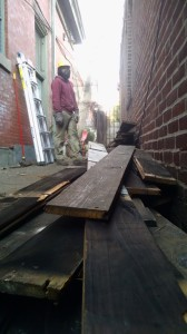 Lanard Hill, a YouthBuild graduate and Philadelphia Community Corps job trainee, standing over a pile of decking. (Credit: Tom Rickert)