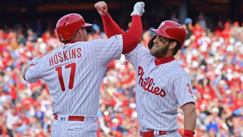 Rhys Hoskins #17 and Bryce Harper #3 of the Philadelphia Phillies celebrate Hoskins grand slam in the seventh inning against the Atlanta Braves on Opening Day at Citizens Bank Park on March 28, 2019 in Philadelphia, Pennsylvania.
